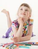 Smiling little girl lying on the floor Royalty Free Stock Image