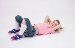 Smiling little girl lying on the floor. White background Royalty Free Stock Images
