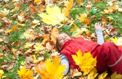 Smiling little girl lying on the grass Royalty Free Stock Images