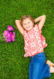 Smiling little girl lying on green grass with flowers Royalty Free Stock Image