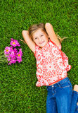 Smiling little girl lying on green grass with flowers Royalty Free Stock Photos