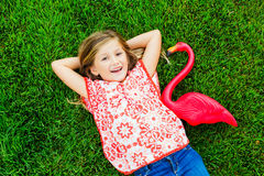Smiling little girl lying on green grass with pink flamingo Royalty Free Stock Photos
