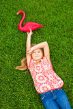 Smiling little girl lying on green grass with pink flamingo Stock Photo