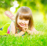 Smiling little girl lying on green grass Stock Image