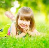 Smiling little girl lying on green grass Stock Image
