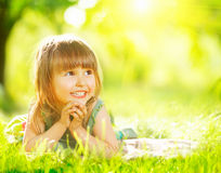 Smiling little girl lying on green grass Stock Photo