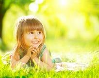 Smiling little girl lying on green grass Stock Photo