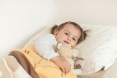 Smiling little girl lying on her bed hugging her favourite soft royalty free stock images