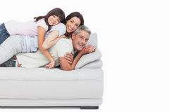 Smiling little girl lying on her parents on sofa Stock Photography