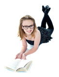 Smiling little girl lying with an open book Stock Photography