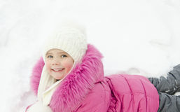Smiling little girl lying in snow Royalty Free Stock Photos