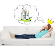 Smiling little girl lying on sofa and dreaming Royalty Free Stock Photography
