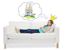 Smiling little girl lying on sofa and dreaming Stock Photos