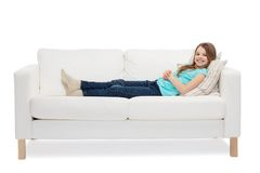 Smiling little girl lying on sofa Stock Photos
