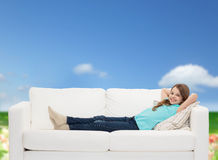Smiling little girl lying on sofa Stock Images