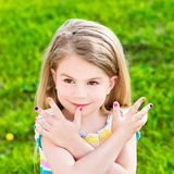 Smiling little girl with many-colored manicure Royalty Free Stock Images