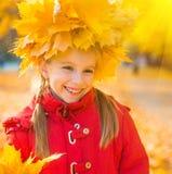 Smiling little girl among  maple leaves Stock Images