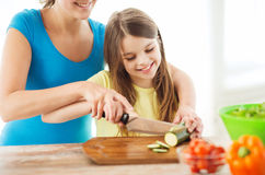 Smiling little girl with mother chopping cucumber Royalty Free Stock Images