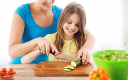 Smiling little girl with mother chopping cucumber Royalty Free Stock Photo