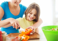 Smiling little girl with mother chopping pepper Stock Image