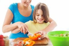 Smiling little girl with mother chopping pepper Stock Images