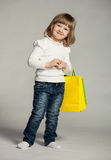 Smiling little girl with multicolored shopping bags Stock Image