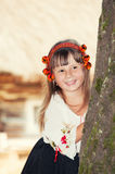 Smiling little girl in the national Ukrainian Hutsul costume and in a wreath looks out from behind a tree Royalty Free Stock Image