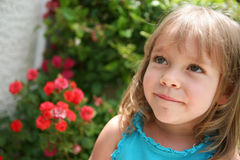 Smiling little girl near red flowers. A little girl smiles in the summer sunshine. Little red flowers are shown nearby Royalty Free Stock Photos