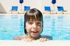 Smiling little girl in an outdoor pool. Smiling little girl looking at camera in an outdoor pool stock photo