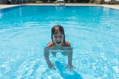 Smiling little girl in an outdoor pool in summer Royalty Free Stock Photography