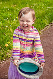 Smiling little girl outdoors holding hat Stock Images