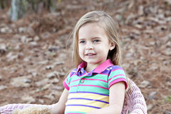 Smiling little girl outdoors in pink chair Royalty Free Stock Photo