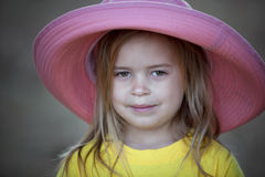 Smiling little girl outdoors in pink hat Royalty Free Stock Image