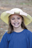 Smiling little girl outdoors wearing hat Stock Photos