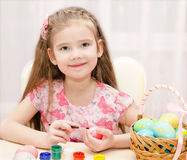 Smiling little girl painting colorful easter eggs Royalty Free Stock Photography