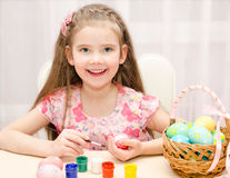 Smiling little girl painting colorful easter eggs Stock Image
