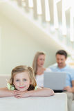 Smiling little girl with parents behind her. Smiling little girl with her parents behind her Royalty Free Stock Image