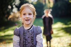 Smiling little girl in park at autumn. With her mother at background Royalty Free Stock Photo