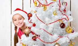 Smiling little girl peeking out from behind a new year tree. Smiling little girl in red hat peeking out from behind a decorated new year tree Royalty Free Stock Image