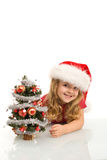 Smiling little girl peeking out a christmas tree. Smiling little girl peeking out a small christmas tree wearing a santa hat - isolated royalty free stock photos