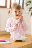 Smiling little girl on phone in lounge Stock Photo