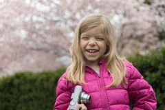 Smiling little girl with photo camera in cherry blossom park in spring. She is happy to enjoy the spring Royalty Free Stock Images