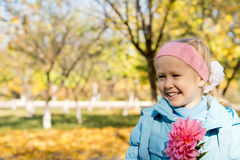 Smiling little girl with pink dahlia Stock Image