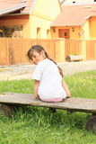 Smiling little girl. In pink trousers and t-shirt sitting on a bench from back Stock Photos