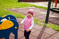 Smiling little girl on playground near swing Royalty Free Stock Image