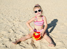 Smiling little girl playing on beach Royalty Free Stock Photos