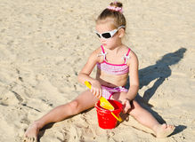 Smiling little girl playing on beach Stock Photography