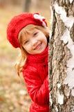 Smiling little girl playing hide and seek. Happy smiling little girl playing hide and seek outdoors peeking birch trunk Royalty Free Stock Image