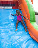 Smiling little girl playing on an inflatable slide bounce house outdoors. Cute smiling little girl playing on an inflatable slide bounce house outdoors. At an Stock Photography