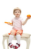 Smiling little girl playing with orange and carrot Royalty Free Stock Image
